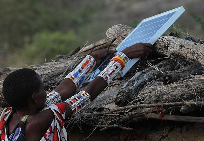 Maasai woman installs solar in Magadi, Kenya to provide light and to protect goats from