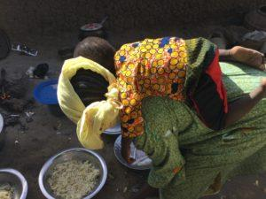 Preparing rice with child on back
