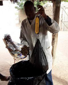 A man weighs a bag under a shelter.
