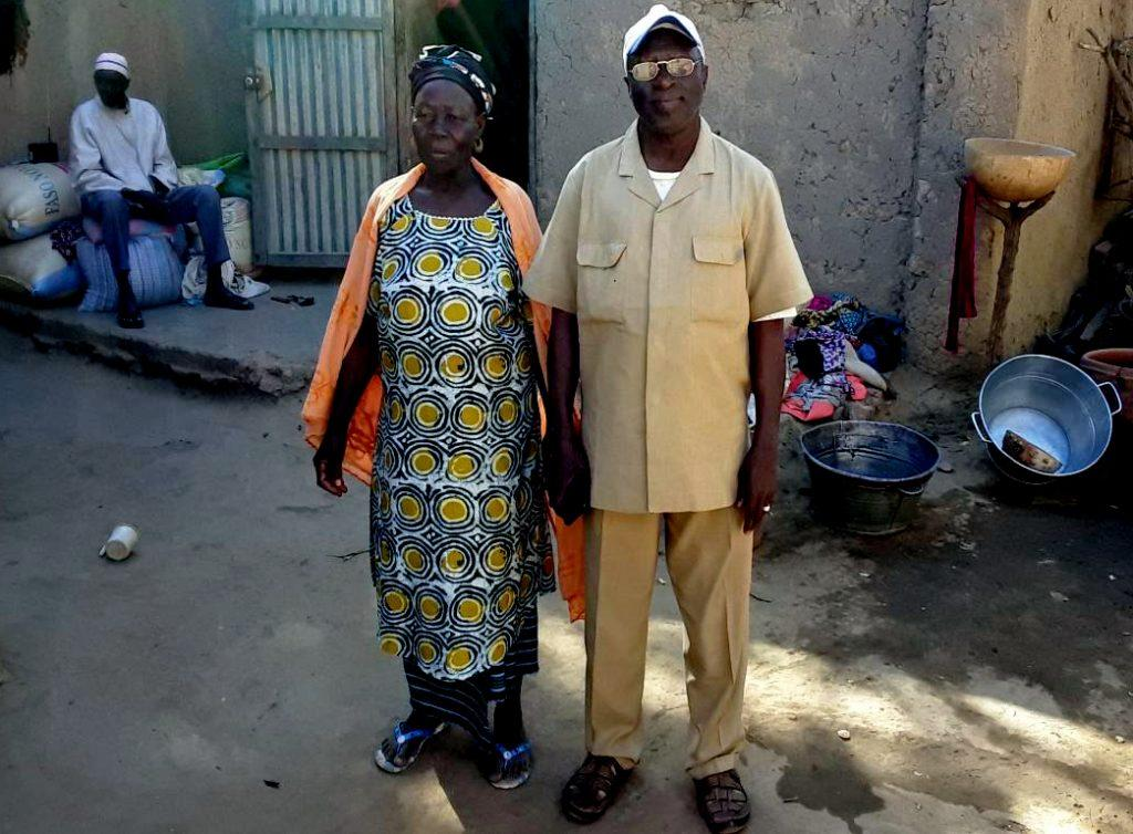 a man and a woman stand next to each other outside a house